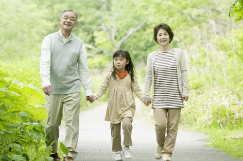 孫と手を繋ぐシニア夫婦