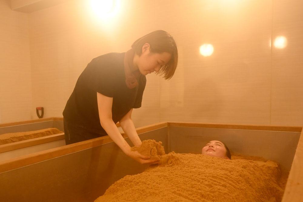温熱木浴を施すスタッフ